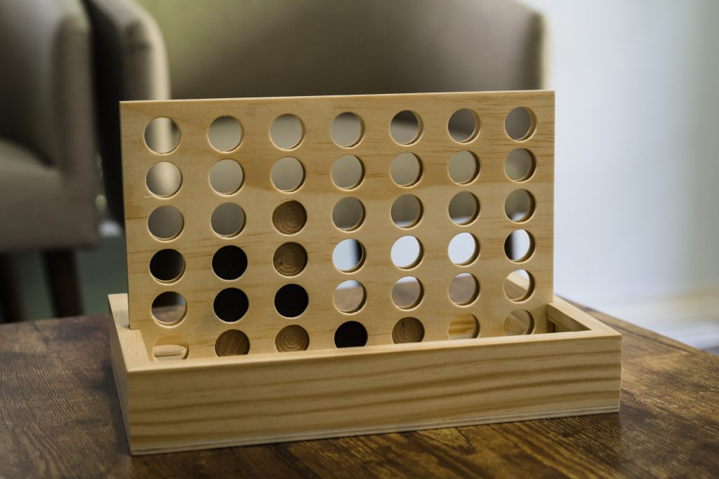 wooden version of connect four with wooden colored and black pieces