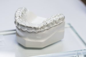 clear thick strong dental night guard stent displayed on model of fake teeth