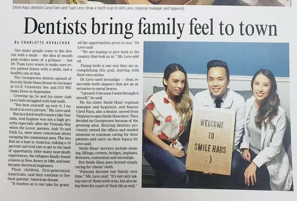 bold title dentists bring family feel to town on williamson county georgetown texas the sun newspaper Dr. Levo Dr. Farn hygienist holding welcoming smile haus sign with news article on side