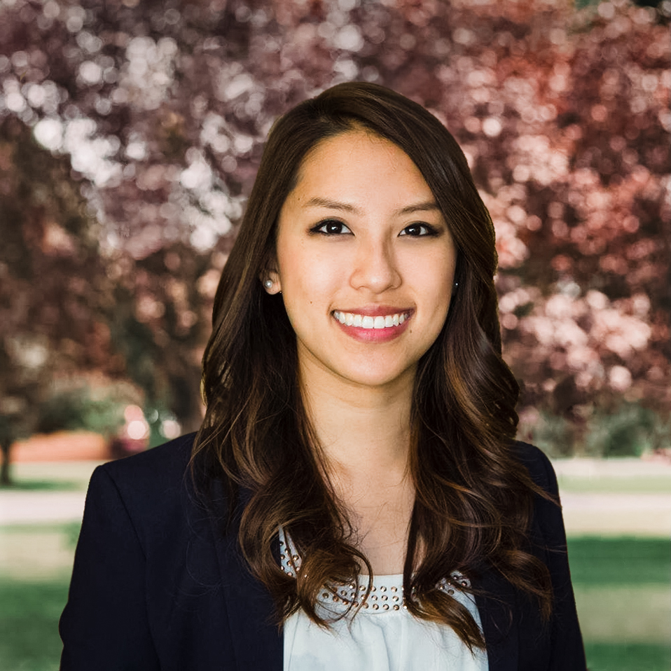 Dr. Carol farn profile picture smiling brightly with straight white teeth wearing white dress shirt and black blazer against tan background very professional