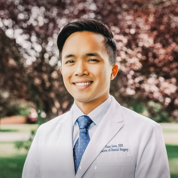 Dr. Tuan Levo smiling with bright white straight teeth smile while wearing professional white coat and light blue tie against nature background with pink flowers